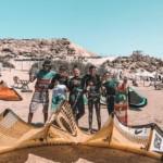 Photo de groupe en cours de kitesurf sur la plage